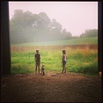 Our 9 and 7 year old daughters (and little Hazel the baby goat) watching the fog roll in from the cornfield, summer 2014